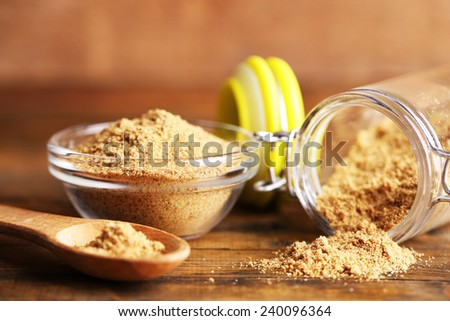 Ground mustard in glass jar and bowl on wooden background - stock photo