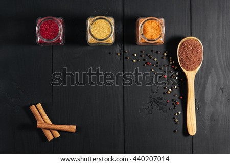 Ground spices in bottles with spon, papper, cinnamon on black wooden background. Top view. Free space. - stock photo