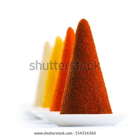 ground spices on white background chilli, paprika, tumeric and ginger cone piles, bright colors. - stock photo