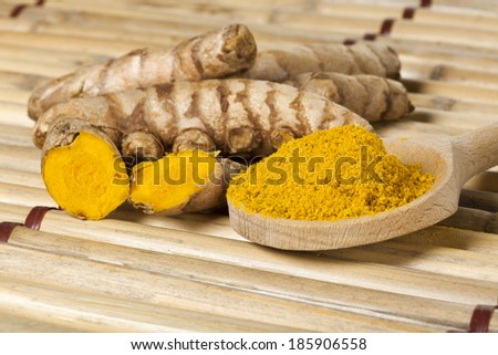 Ground turmeric on wooden spoon and turmeric roots on bamboo mat - stock photo