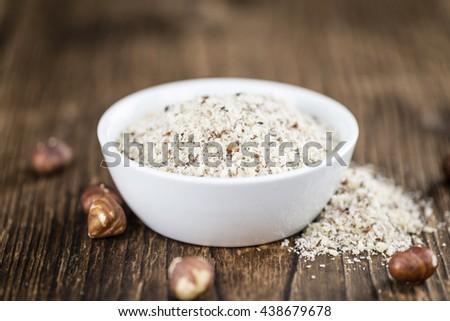 Grounded Hazelnuts (selective focus; close-up shot) on vintage background - stock photo