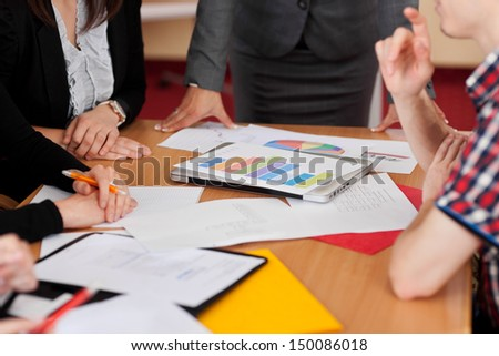 Group activity and teamwork with a group of business colleagues seated around a table having a brainstorming session with analytical graphs - stock photo