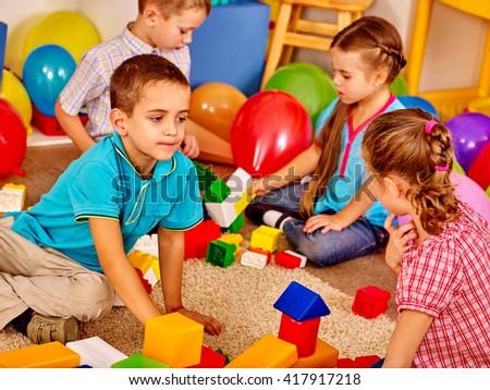 Group children game blocks on floor in kindergarten . Children play together. - stock photo
