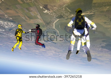 Group collects figure skydivers in freefall. - stock photo