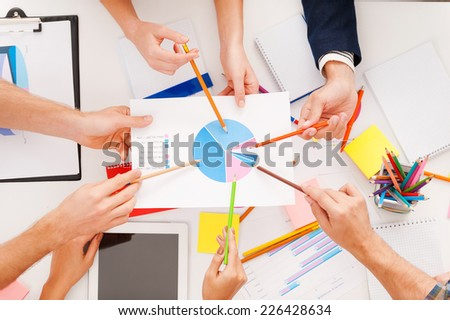 Group discussion. Top view of business people pointing diagram together while sitting at the table - stock photo