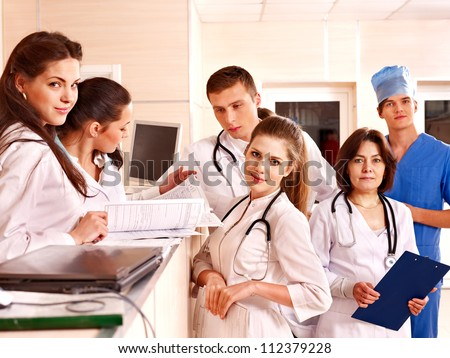 Group doctors and patient standing at reception in hospital. - stock photo