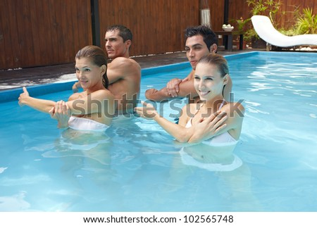 Group doing water aerobics in blue swimming pool - stock photo