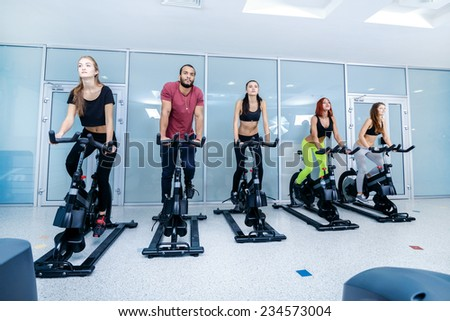 Group exercises in the gym. Five sports friends pedaling and looks in front of a stationary bicycles at the gym. Athletes dressed in sports clothes - stock photo