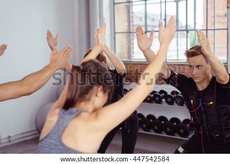 Group exercising by tall windows in fitness studio while wearing ems outfits - stock photo
