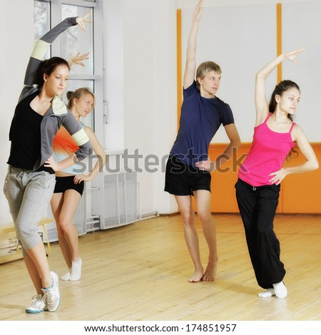 Group exercising in gym bending left