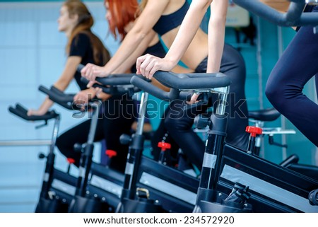 Group fitness riding a exercise bikes. Three athletes girlfriend pedaling on a stationary bike at the gym. Close-up view of simulators - stock photo
