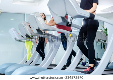Group fitness sessions on the treadmill. Sports people running on the treadmill at the gym. Athletes wearing sportswear and running in the gym. - stock photo