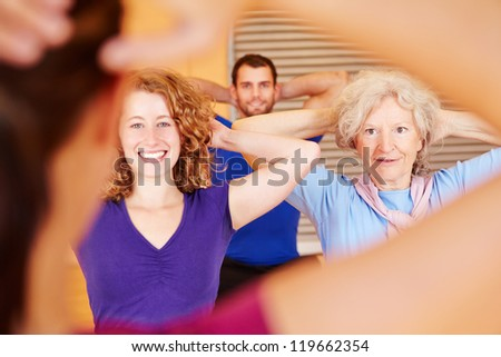 Group following fitness trainer instructions in a gym - stock photo
