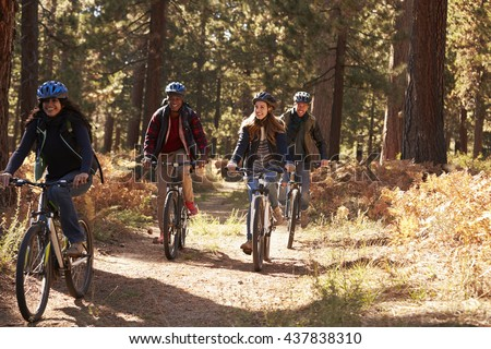 Group four friends in helmets riding bikes on a forest path - stock photo