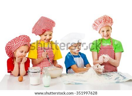 Group funny kids preparing cake dough - stock photo