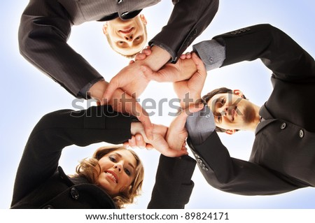 Group handshake with a lot of different hands over blue background - stock photo