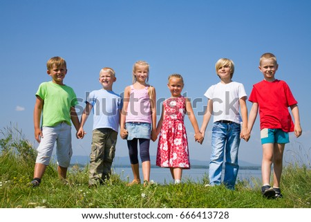 Group  happy children  standing on summer meadow against blue sky