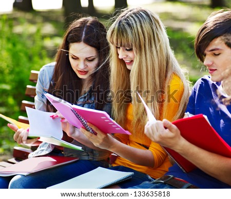 Group happy student with notebook on bench outdoor. - stock photo