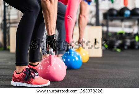 Group having functional fitness training with kettlebell in sport gym - stock photo