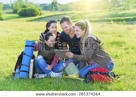 Group hikers on the grass with backpack used tablet pc, summer outdoor. Adventure, travel, tourism, hike and people concept. - stock photo