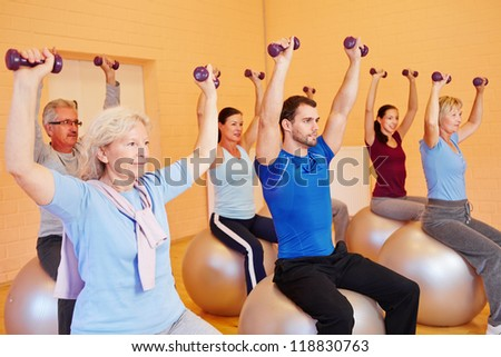 Group in fitness center doing dumbbell training sitting on gym balls