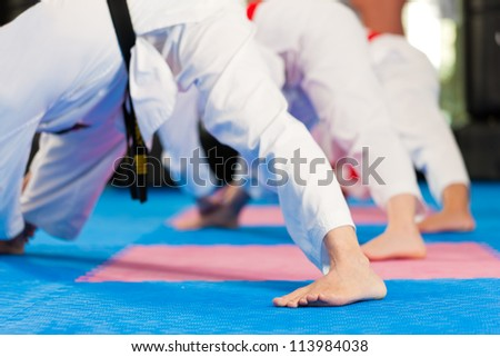Group in martial art training in a gym, she is stretching and warming up - stock photo