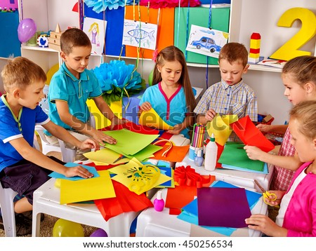 Group kids are making something out of colored paper in primary school.