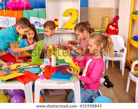 Group kids holding colored paper on table in kindergarten .Children learn together in kindergarten.