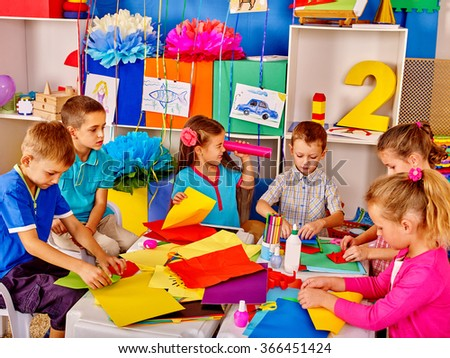 Group kids male and female holding colored paper on table in kindergarten . - stock photo