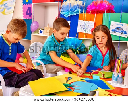 Group kids of three people making colored paper on table in kindergarten . - stock photo