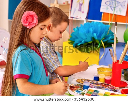 Group kids  with brush painting on table in  kindergarten .  - stock photo