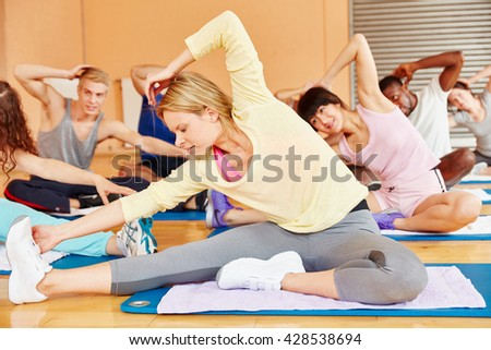 Group making gymnastics exercise in fitness center - stock photo