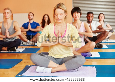 Group meditating together in yoga class at fitness center - stock photo