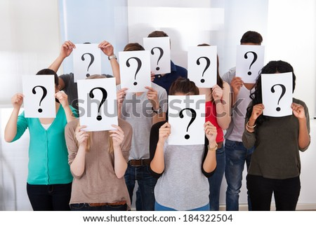 Group multiethnic university students holding question mark signs in front of their faces - stock photo