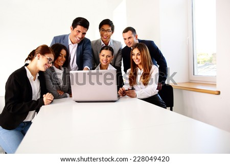 Group of a happy businesspeople working on the laptop at meeting - stock photo
