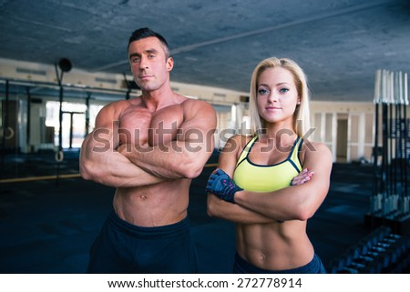 Group of a muscular man and fitness woman standing with arms folded in gym - stock photo