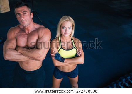 Group of a muscular man and fitness woman standing with arms folded in gym. Looking at camera  - stock photo
