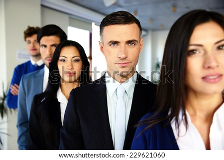 Group of a serious business people standing in a row in office - stock photo