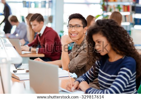 Group of a students studying in the university library - stock photo