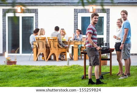 Group of a young friends preparing a barbecue in a back yard - stock photo