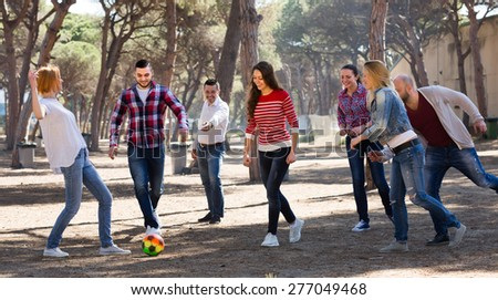 Group of active friends playing football at picnic lunch. Selective focus