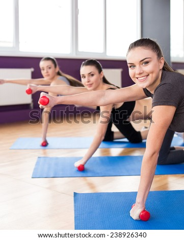 Group of active smiling women are training in fitness club with dumbbells. Smiling and looking at the camera. - stock photo
