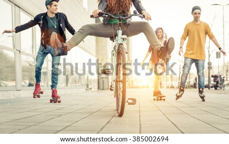 Group of active teenagers in town. four teens making recreational activity in an urban area - stock photo