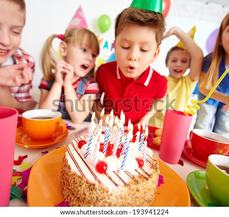 Group of adorable kids looking at birthday cake with candles, cute boy blowing on them - stock photo