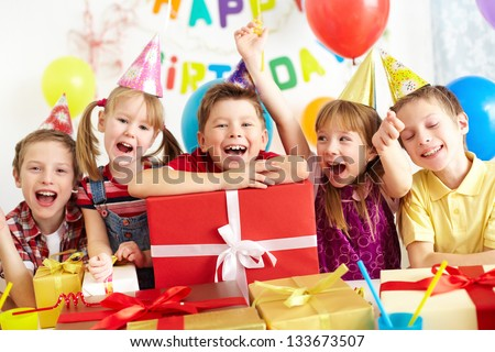 Group of adorable kids looking at camera with giftboxes near by