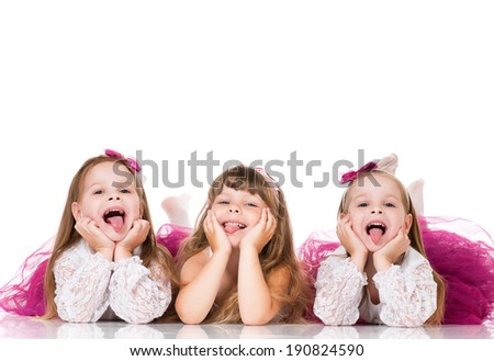 Group of adorable little girls having fun lying on floor, isolated on white background - stock photo