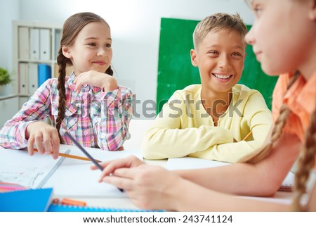Group of adorable schoolmates discussing ideas at drawing lesson - stock photo