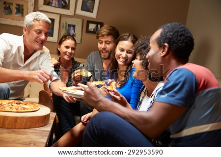 Group of adult friends eating pizza at a house party - stock photo