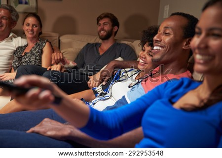 Group of adult friends watching television together - stock photo