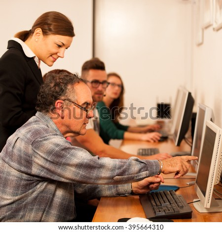 Group of adults learning computer skills. Inter generational transfer of knowledge. - stock photo